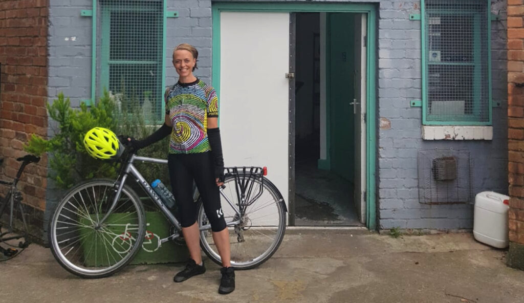 Clare stood with her bike, smiling in front of Bikeworks Nottingham