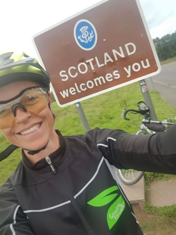 Clare in front of a Scotland welcomes you sign