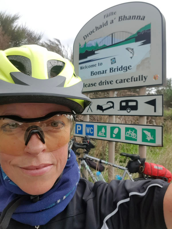 Clare in front of a sign for Bonar Bridge