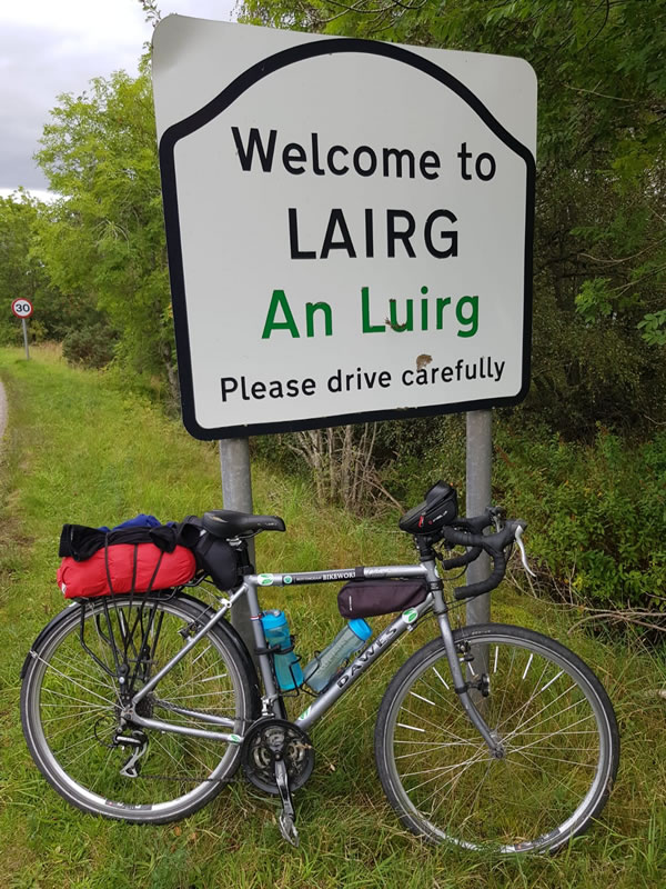 Clare's bike in front of a sign sayng Welcome to Lairg