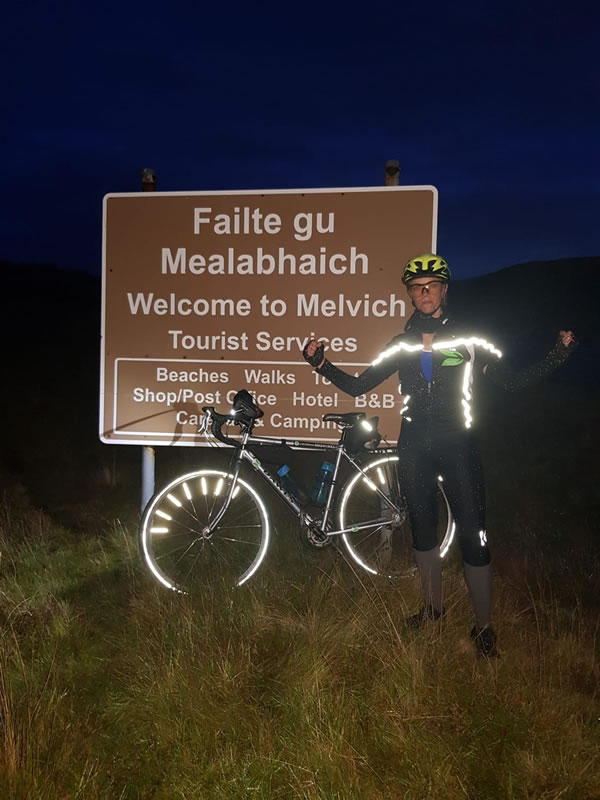 Clare at nigh time in front of a sign saying Welcome to Melvich