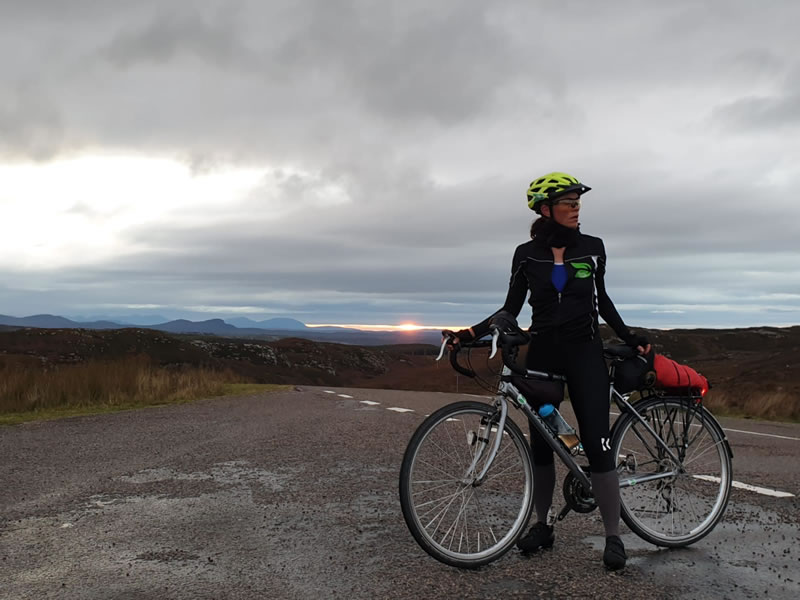 Clare stood with her bike and a beautiful sunset and scenery in the background