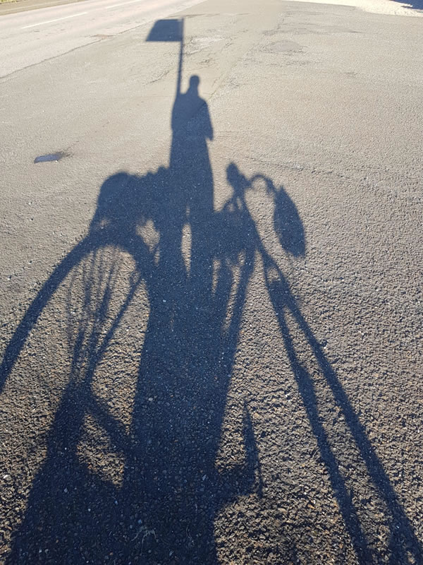 A silhouette of Clare's bike in front of the John o'Groats sign