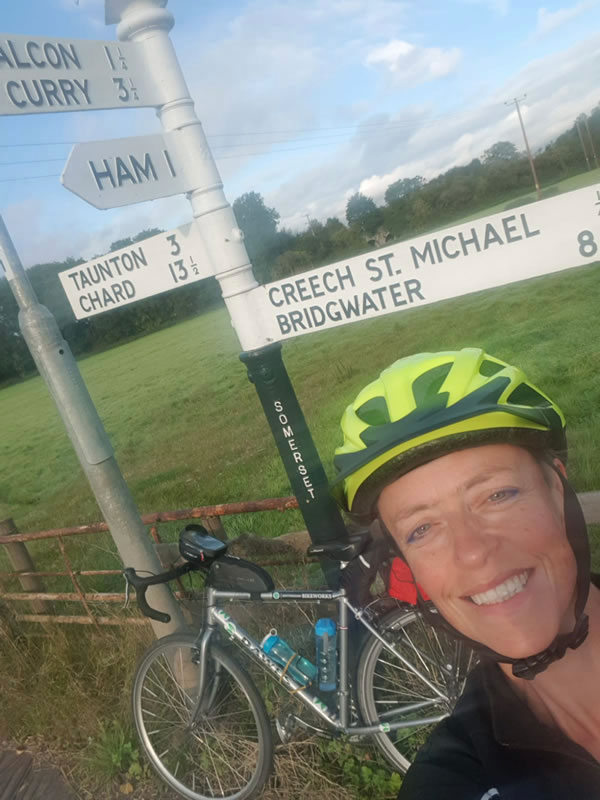 Clare smiling in front of a road sign showing Bridgwater